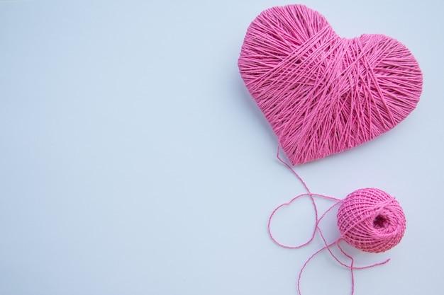 Bola de fio colorido isolada. coração rosa como um símbolo do amor. hobby. copyspace