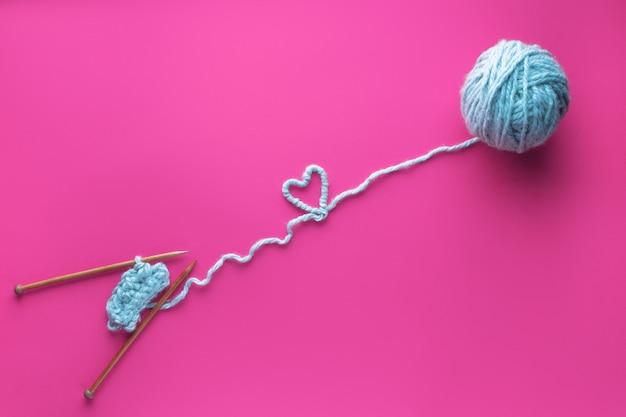 Bola de fio e agulhas de tricô em fundo rosa. conceito artesanal e bordado.