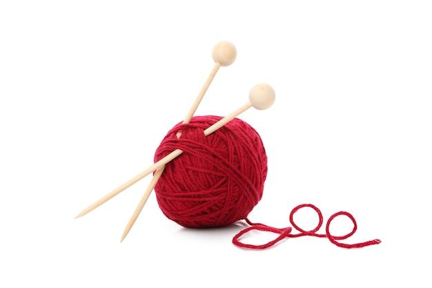 Bola de fio vermelho com agulhas de tricô, isolada no fundo branco.