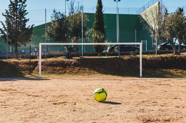 Bola de futebol amarela colocada em posição de lance livre. campo de futebol de campo.