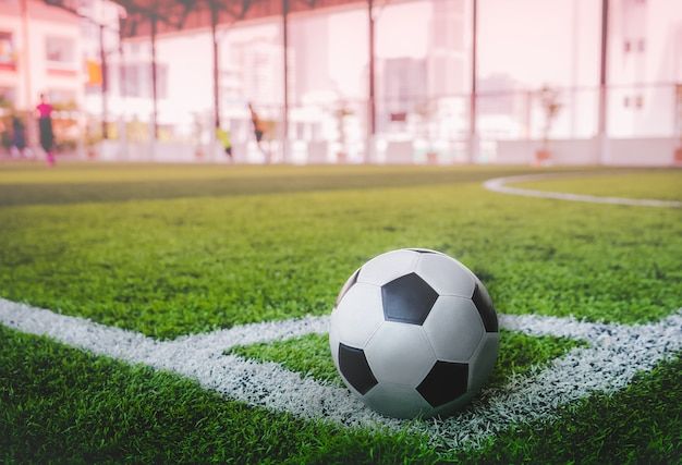 Bola de futebol clássica preta e branca usada no canto do campo de futebol
