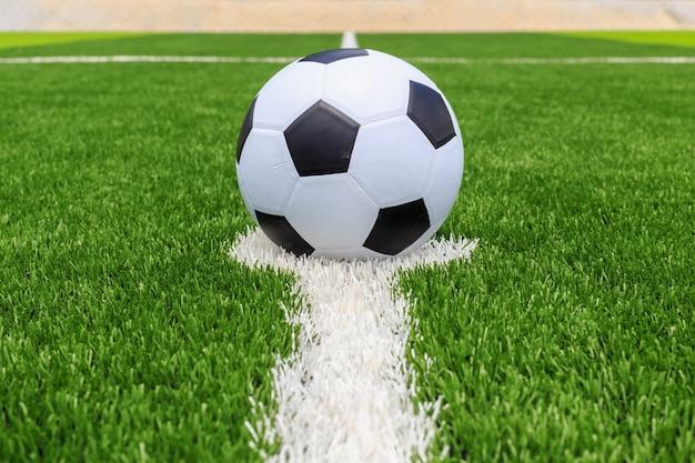 Bola de futebol clássico na relva verde escura e brilhante artificial