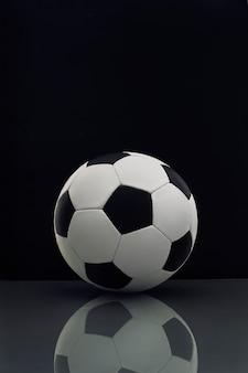 Bola de futebol com reflexo na mesa no escuro Foto Premium