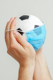 Bola de futebol com uma máscara médica
