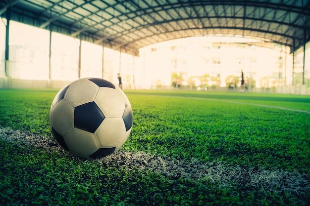 Bola de futebol deitado em uma linha de fronteira branca em um campo de futebol.
