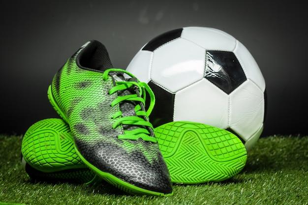 Bola de futebol e chuteiras no campo de futebol