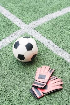 Bola de futebol e luvas de couro de jogador de futebol em campo verde para partidas com linhas brancas cruzadas