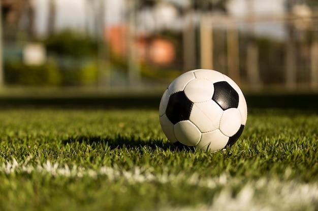 Bola de futebol em um campo gramado, sob o pôr do sol