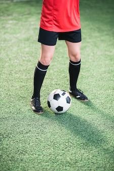 Bola de futebol entre as pernas da garota ativa com uniforme esportivo em pé no campo de futebol verde durante o treinamento