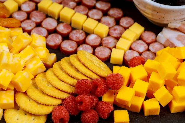Bola de futebol feita de linguiça e queijo no tabuleiro de charcutaria para festa de jogo de futebol americano