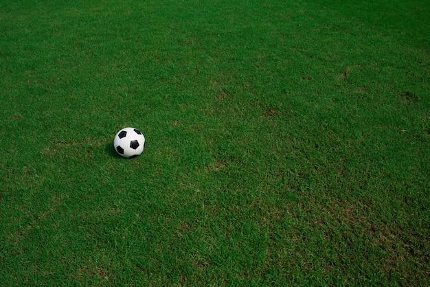 Bola de futebol na grama com fundo do estádio