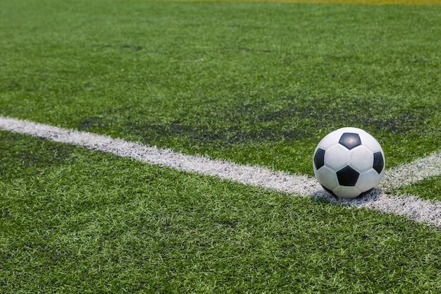 Bola de futebol na linha branca no fundo de grama de campo de futebol verde