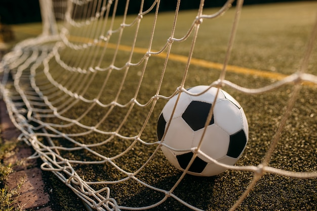Bola de futebol na rede do portão. futebol em estádio ao ar livre, jogo de esporte ou conceito de gol