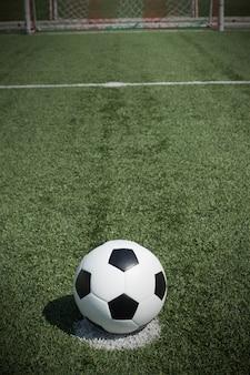 Bola de futebol no campo com goalnet na frente