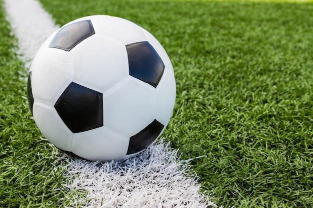 Bola de futebol no campo no fundo da linha branca