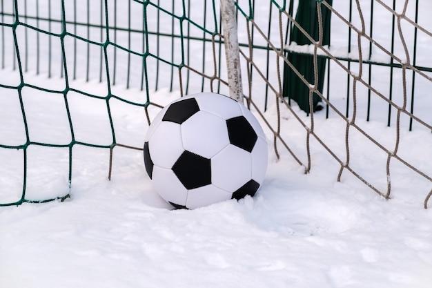 Bola de futebol no canto do gol de futebol no inverno
