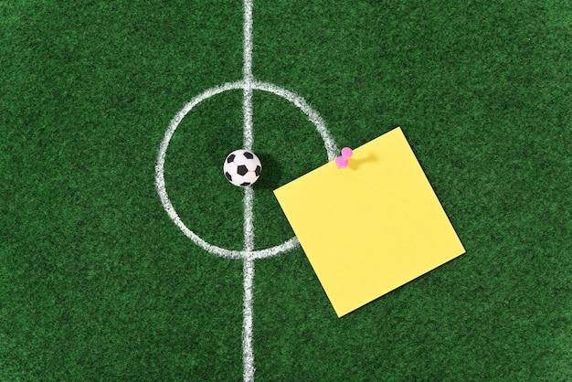 Bola de futebol no centro do campo de futebol e alfinetes de papelaria