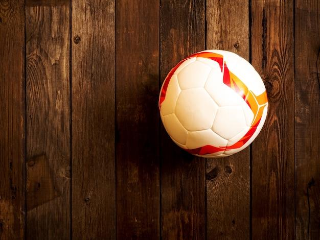 Bola de futebol no fundo de madeira. vista do topo