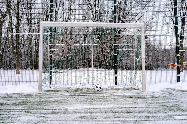 Bola de futebol perto da baliza de futebol no inverno