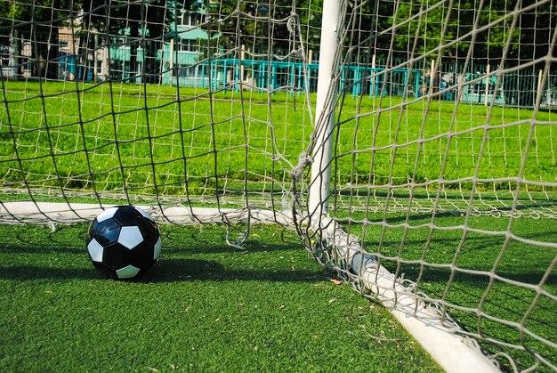 Bola de futebol preta na rede do gol em um gramado verde em um dia ensolarado de verão.