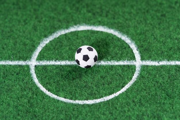 Bola de futebol preto e branco no centro da decoração do campo de futebol mini