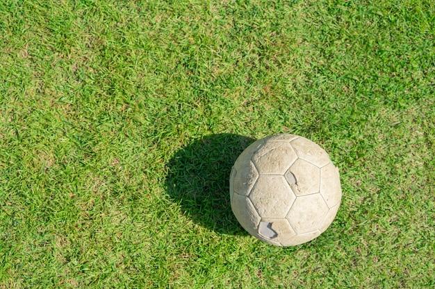Bola de futebol velha na grama verde do campo de futebol. futebol vintage.