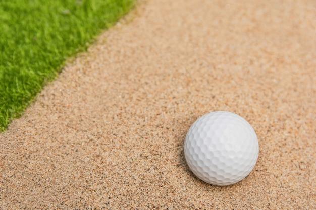 Bola de golfe branca no bunker de areia no campo de golfe