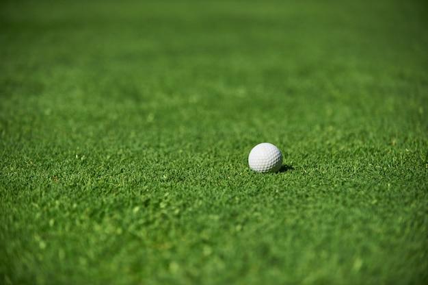 Bola de golfe branco em campo verde close-up