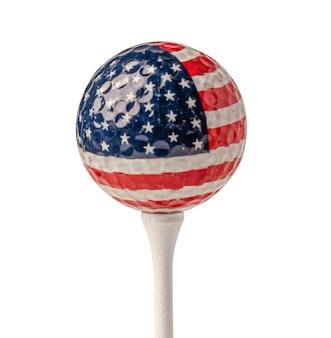 Bola de golfe com a bandeira dos eua no tee branco com traçado de recorte.