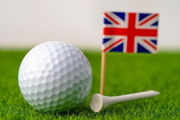 Bola de golfe com bandeira do reino unido no gramado verde.