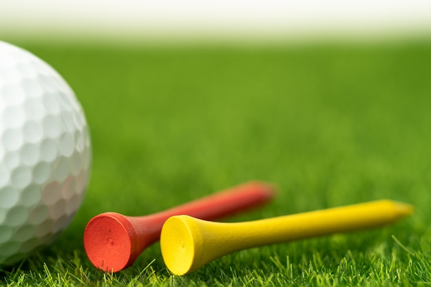 Bola de golfe com tee na grama verde
