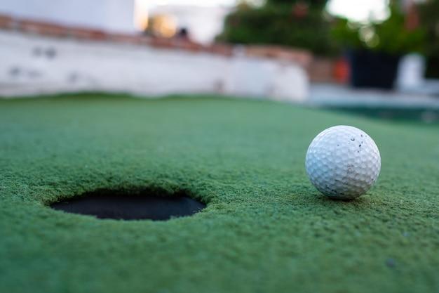 Bola de golfe e buraco em um campo de minigolfe
