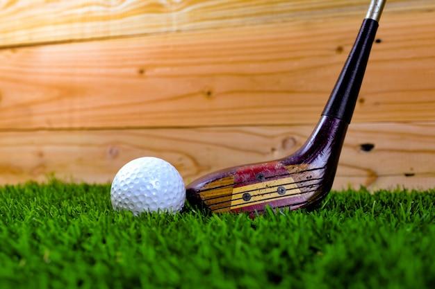 Bola de golfe e clube de golfe na grama com parede de madeira