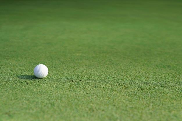 Bola de golfe em uma grama verde com espaço em branco da cópia