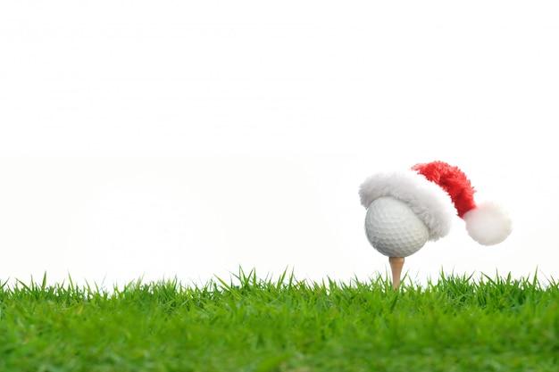 Bola de golfe festiva no tee com chapéu de papai noel no topo para a temporada de férias isolada no branco