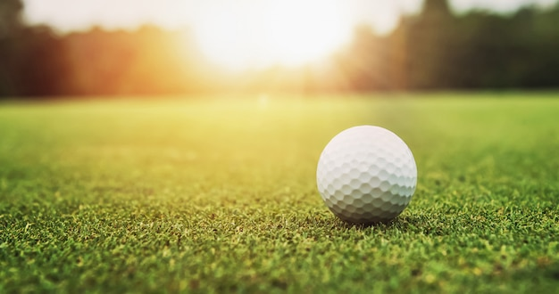 Bola de golfe na grama verde fundo por do sol