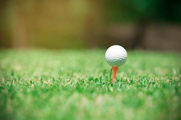 Bola de golfe no tee pronto para ser baleado. bola de golfe em fundo de quintal de clube de golfe de grama verde
