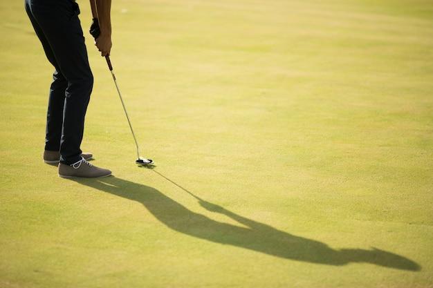 Bola de golfe, taco e pernas do menino em verde