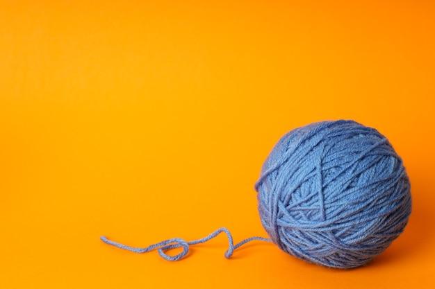 Bola de lã azul em fundo laranja.