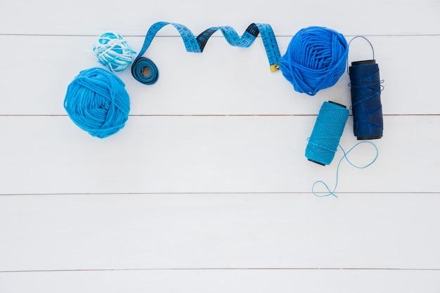 Bola de lã azul; fita métrica e fio de carretel na mesa de madeira