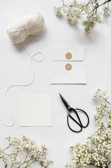Bola de lã; tesoura; envelope e flores da respiração do bebê no fundo branco
