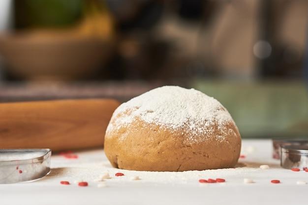 Bola de massa crua polvilhada com farinha na mesa