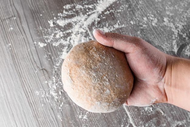 Bola de massa de trigo com farinha nas mãos
