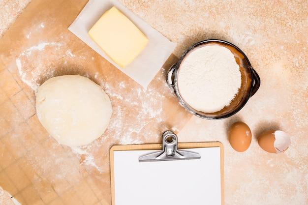 Bola de massa; farinha; bloco de manteiga; ovos e prancheta sobre o pano de fundo da cozinha