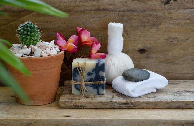 Bola de massagem com ervas e sabonete de índigo spa produtos de aromaterapia decoração com pote de cacto na mesa de madeira