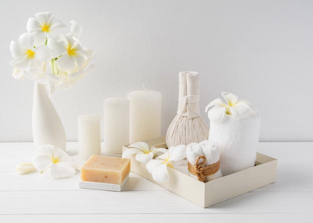 Bola de massagem de composição de spa, flor de plumeria em um vaso, sabonete de café com coco, toalhas brancas e vela no fundo da mesa de madeira branca, tom branco suave natureza morta
