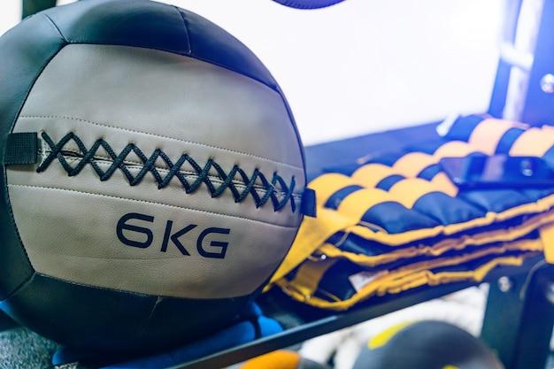 Bola de mecidina cinza com 6 kg de peso e outros equipamentos esportivos na academia.