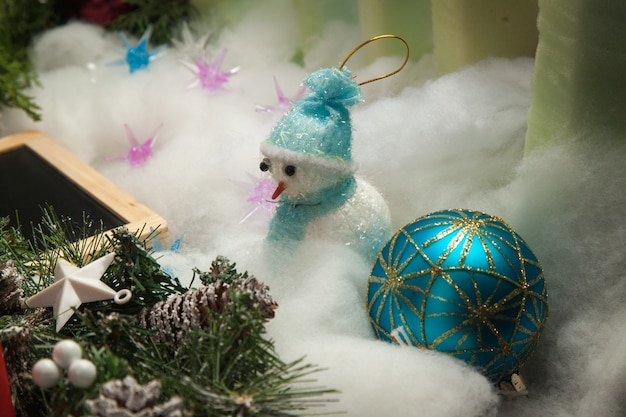 Bola de natal azul com boneco de neve decorada com um galho de pinheiro na neve artificial