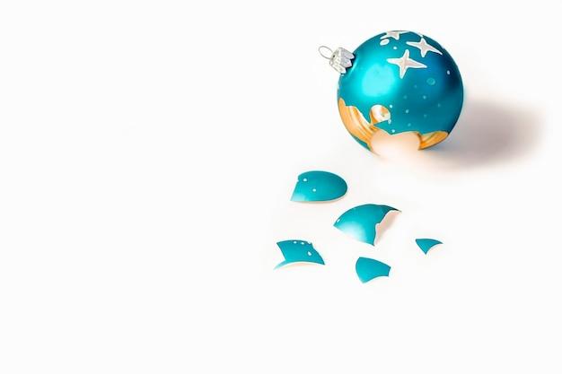 Bola de natal azul quebrada em fundo branco como um símbolo de destruição