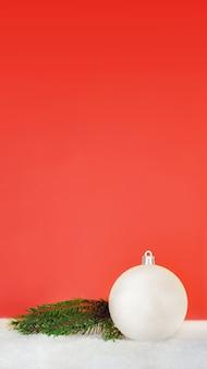 Bola de natal branco e ramo de abeto em um fundo vermelho, cartão de ano novo